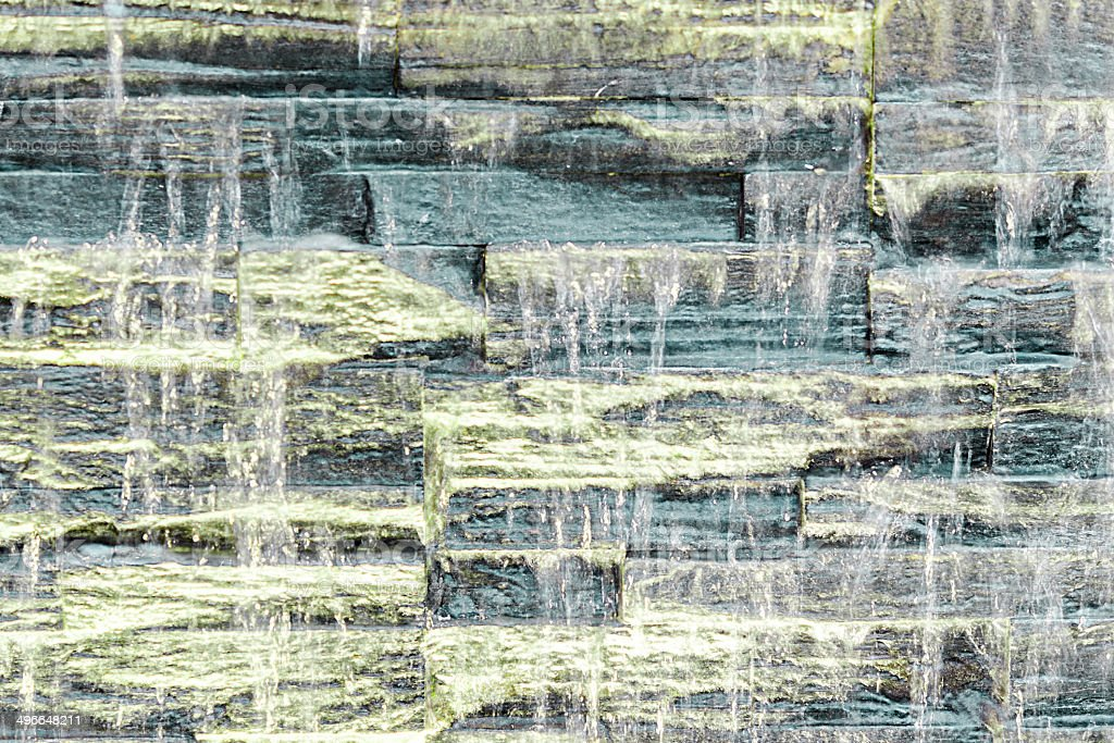 Backlit waterfall against rough stone wall texture stock photo