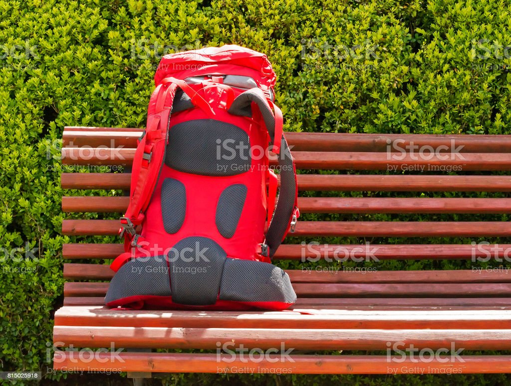 Backpack close up on the bench in the garden. Travel concept. Backpacker style stock photo