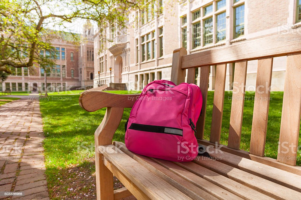 Backpack laying on university bench stock photo