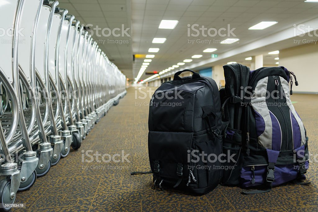 backpack luggage and cart with airport terminal background stock photo