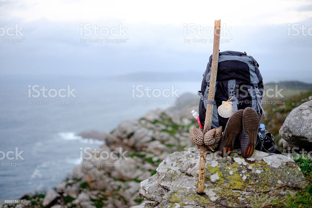 Backpack overlooking the Finisterre cliffs on the Camino de Santiago stock photo