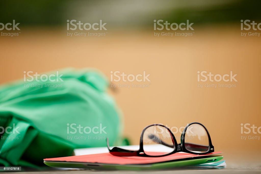Backpack with glasses and book lying on wooden board stock photo