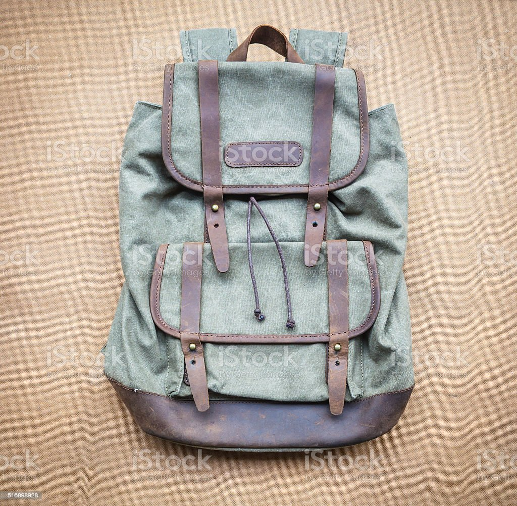 Backpack with leather elements on wood board background stock photo
