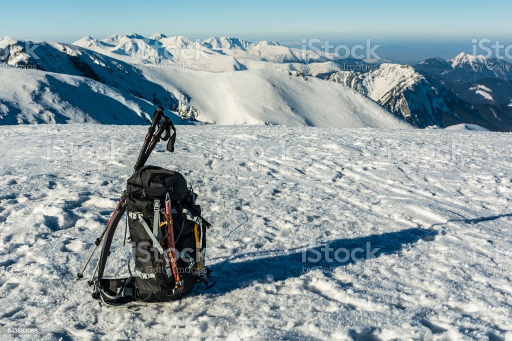 Backpack with the referenced ice axes and trekking poles. stock photo