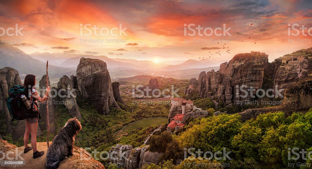 backpacker and a dog in a breathtaking landscape stock photo