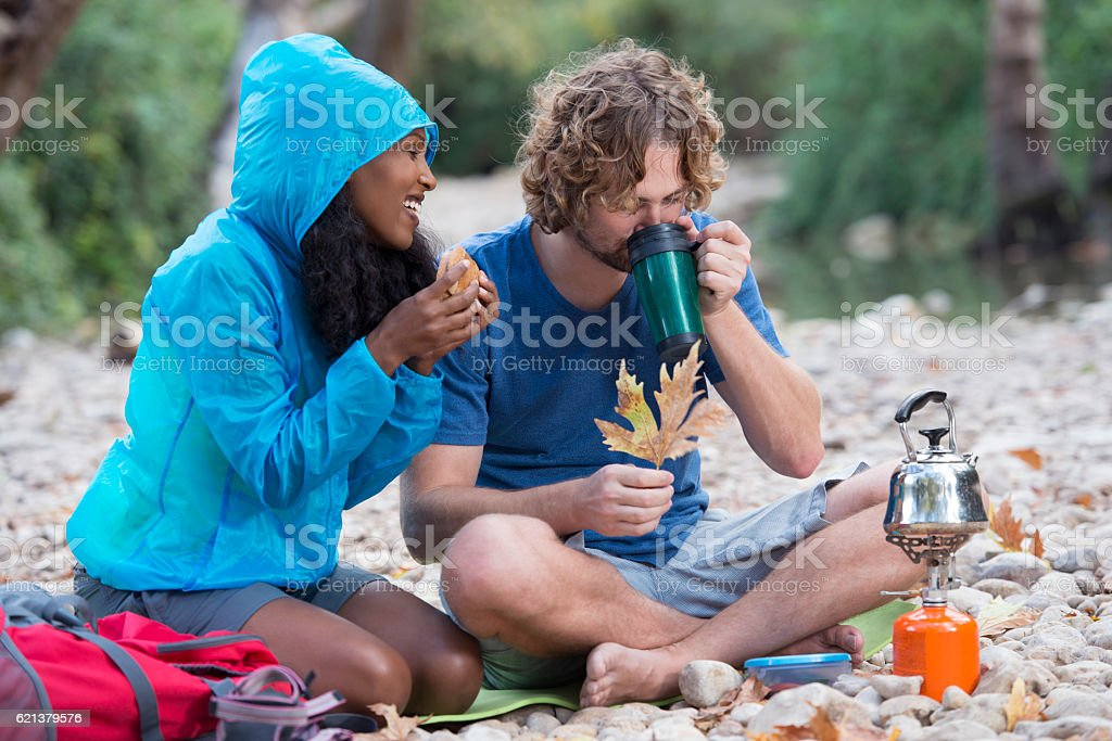 Backpacker couple having coffee break outdoor. stock photo