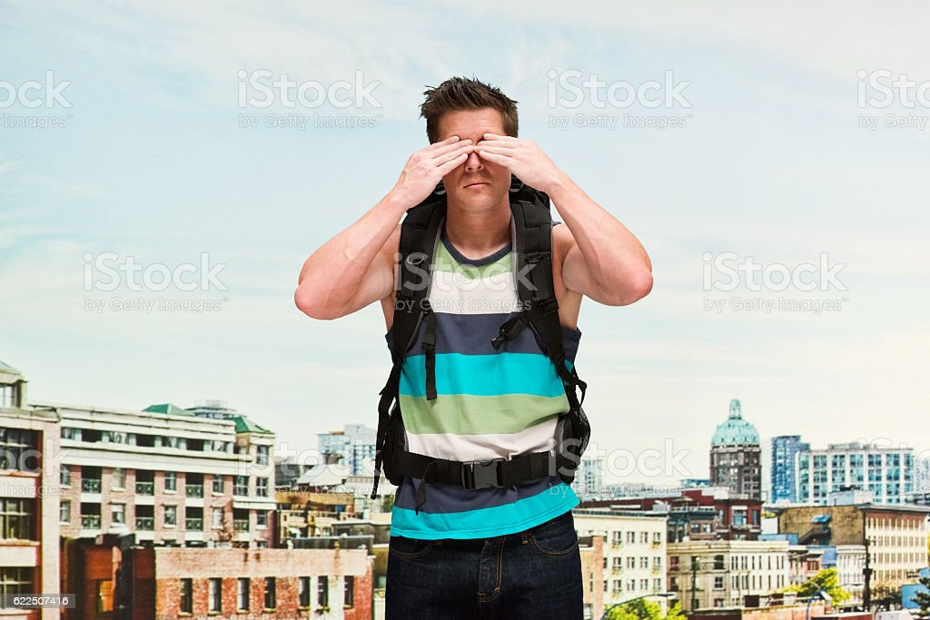 Backpacker covering his eyes in front of city stock photo