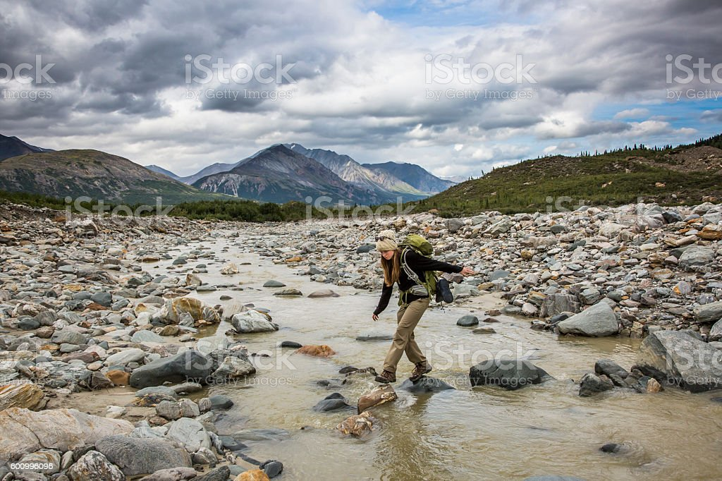 Backpacker crossing river in remote mountain wilderness, Alaska stock photo