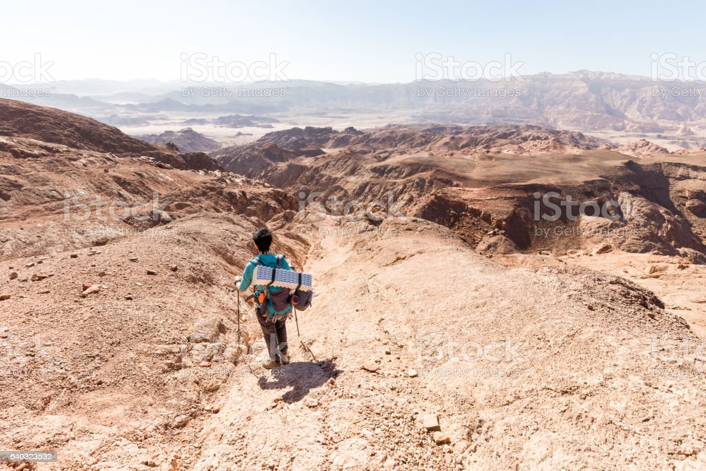 backpacker descending  hiking mountain ridge stone desert landscape. stock photo