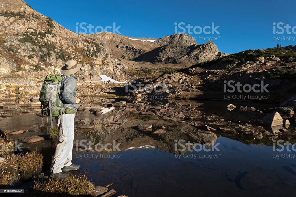 Backpacker explores mountain lake Indian Peaks Wilderness Continental Divide Colorado stock photo