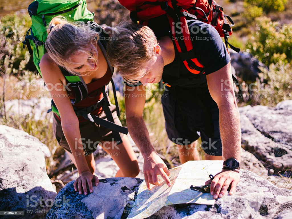 Backpacker friends reading map on hiking trip in mountains stock photo