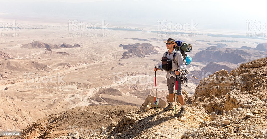 Backpacker guy standing trail looking mountains desert view. stock photo