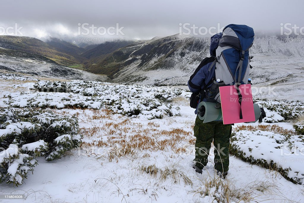 Backpacker in winter mountains stock photo