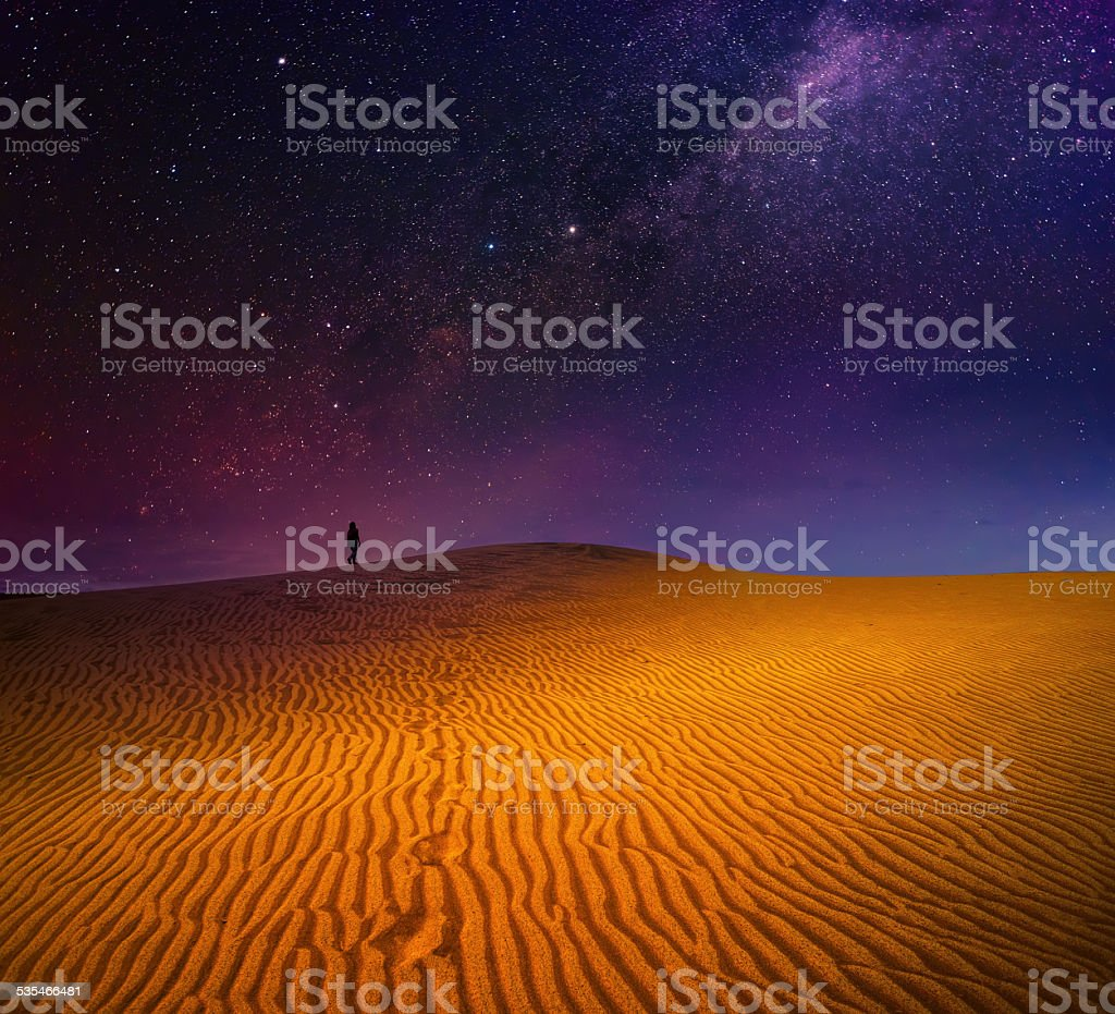 Backpacker is walking among sandy dunes under the starry sky stock photo