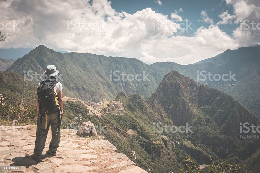 Backpacker looking at Machu Picchu, Peru, toned image stock photo