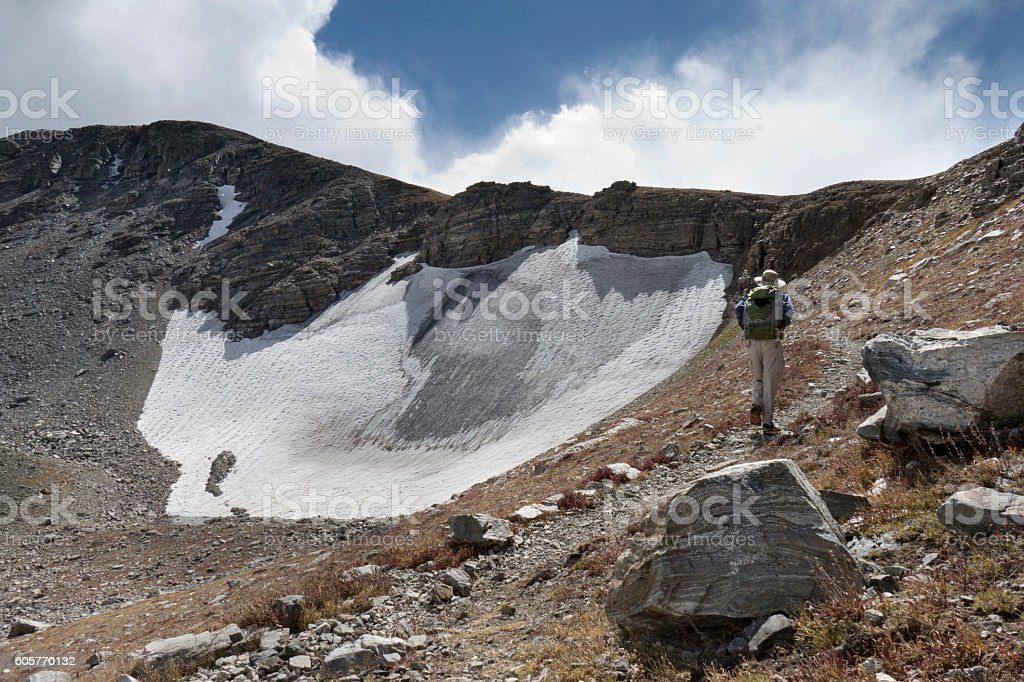 Backpacker man hiking Indian Peaks Wilderness Sawtooth Mountain snowfield Colorado stock photo