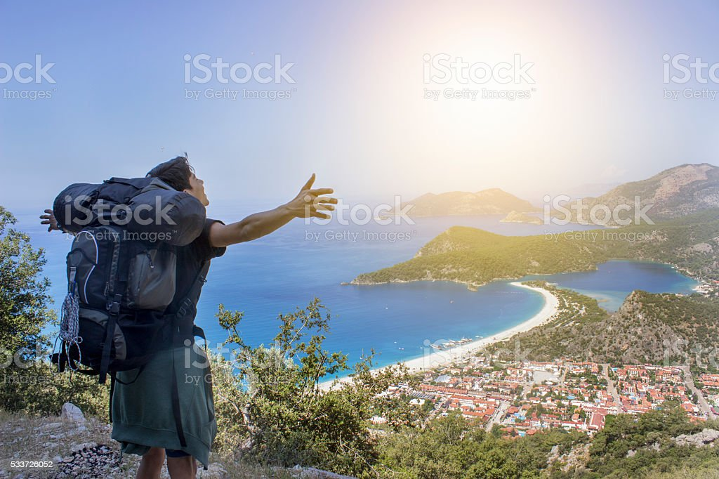 Backpacker opening his arms against Fethiye's beauty landscape stock photo