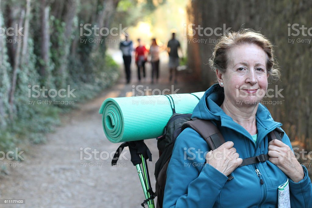 Backpacker senior woman with backpack hiking stock photo