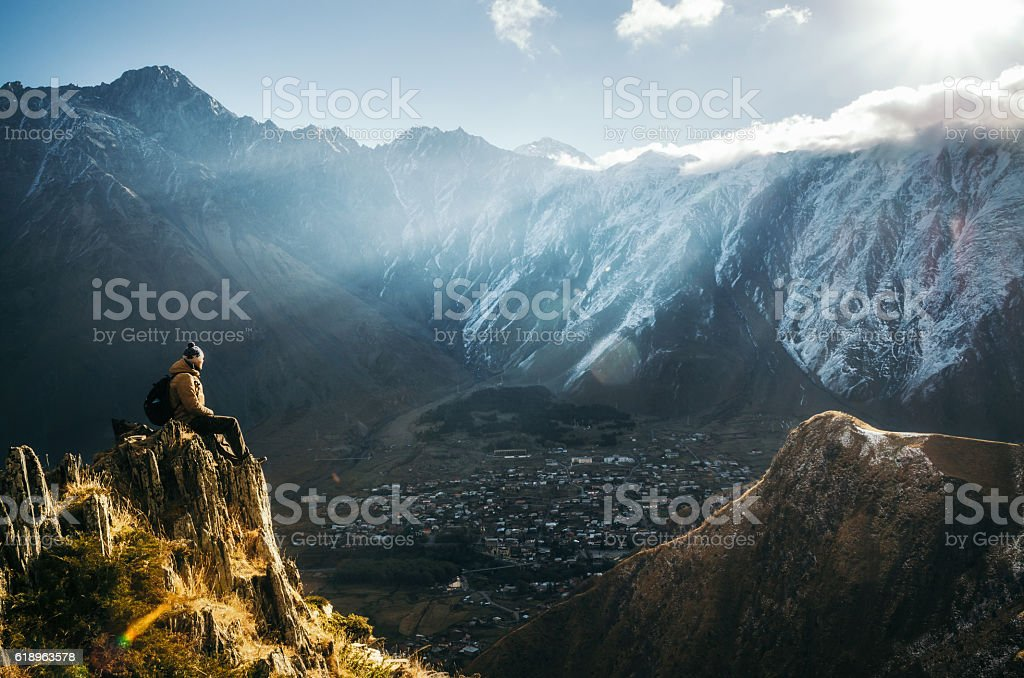 Backpacker sit on cliff edge and looks at mount valley stock photo