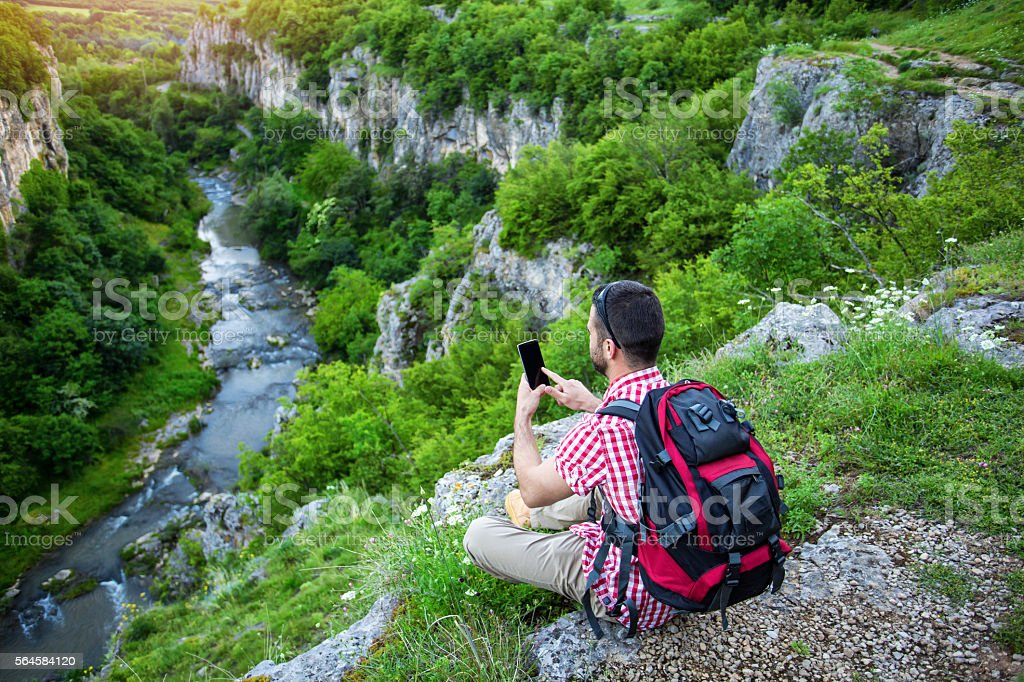 Backpacker sitting on mountain peak and typing on phone stock photo