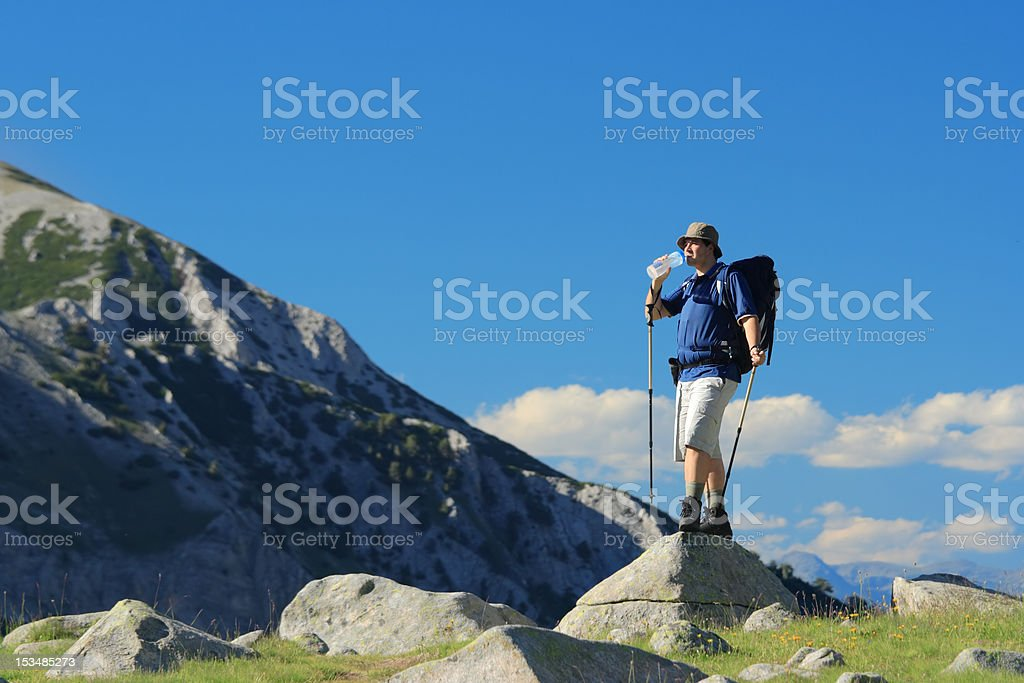 Backpacker standing on a rock royalty-free stock photo