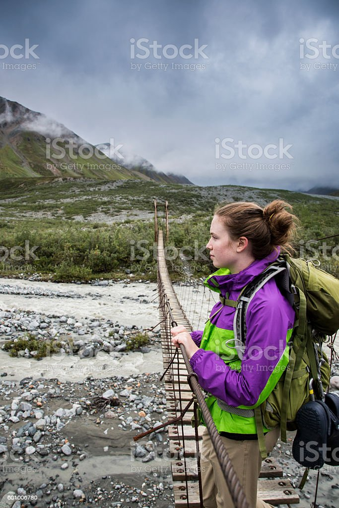 Backpacker standing on Suspension Bridge looking out at Mountain stock photo