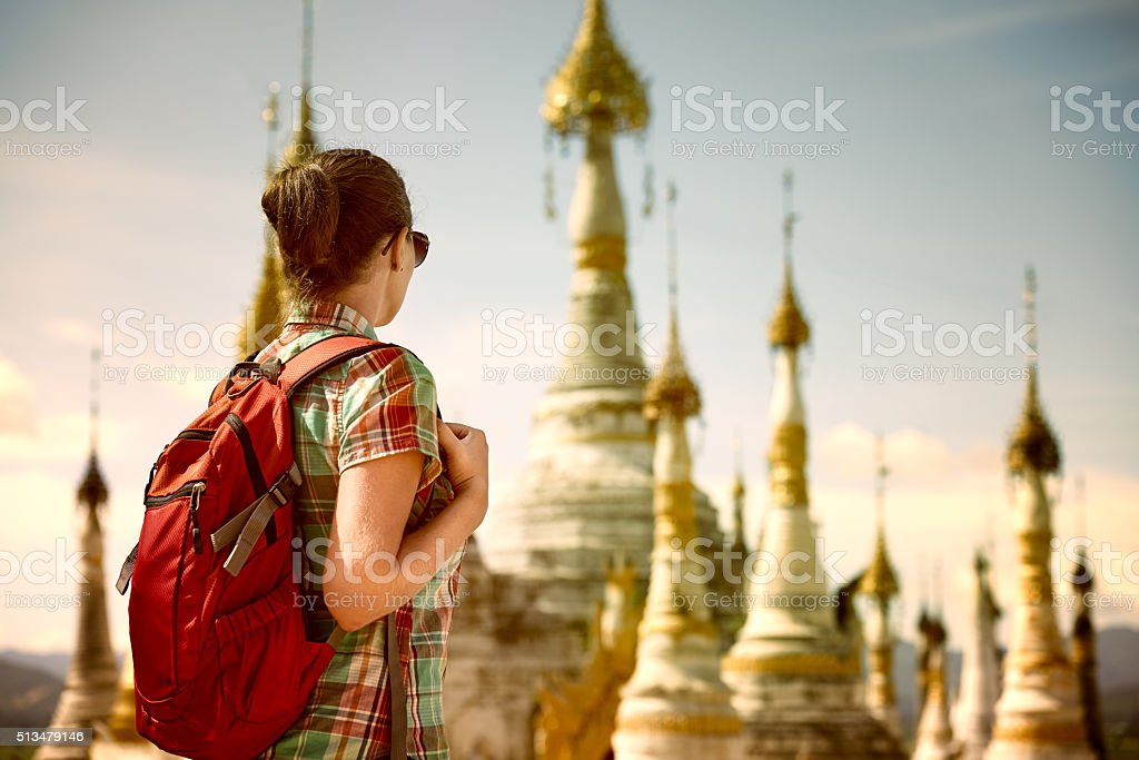 Backpacker traveling  with backpack and looks at Buddhist stupas stock photo