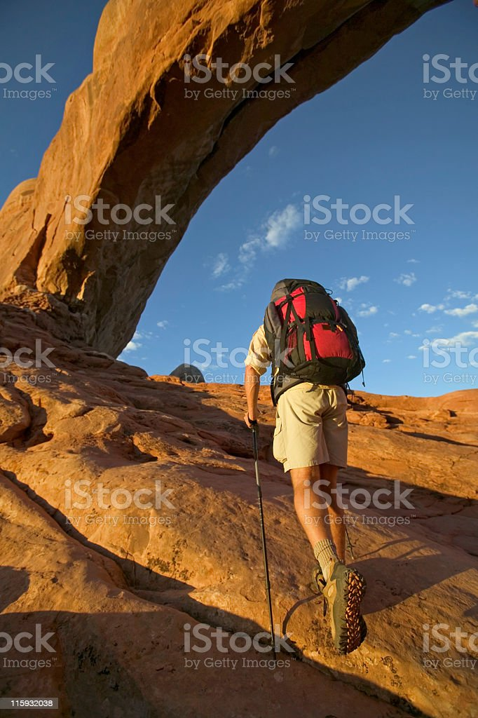 Backpacker under Arch in Moab, Utah royalty-free stock photo