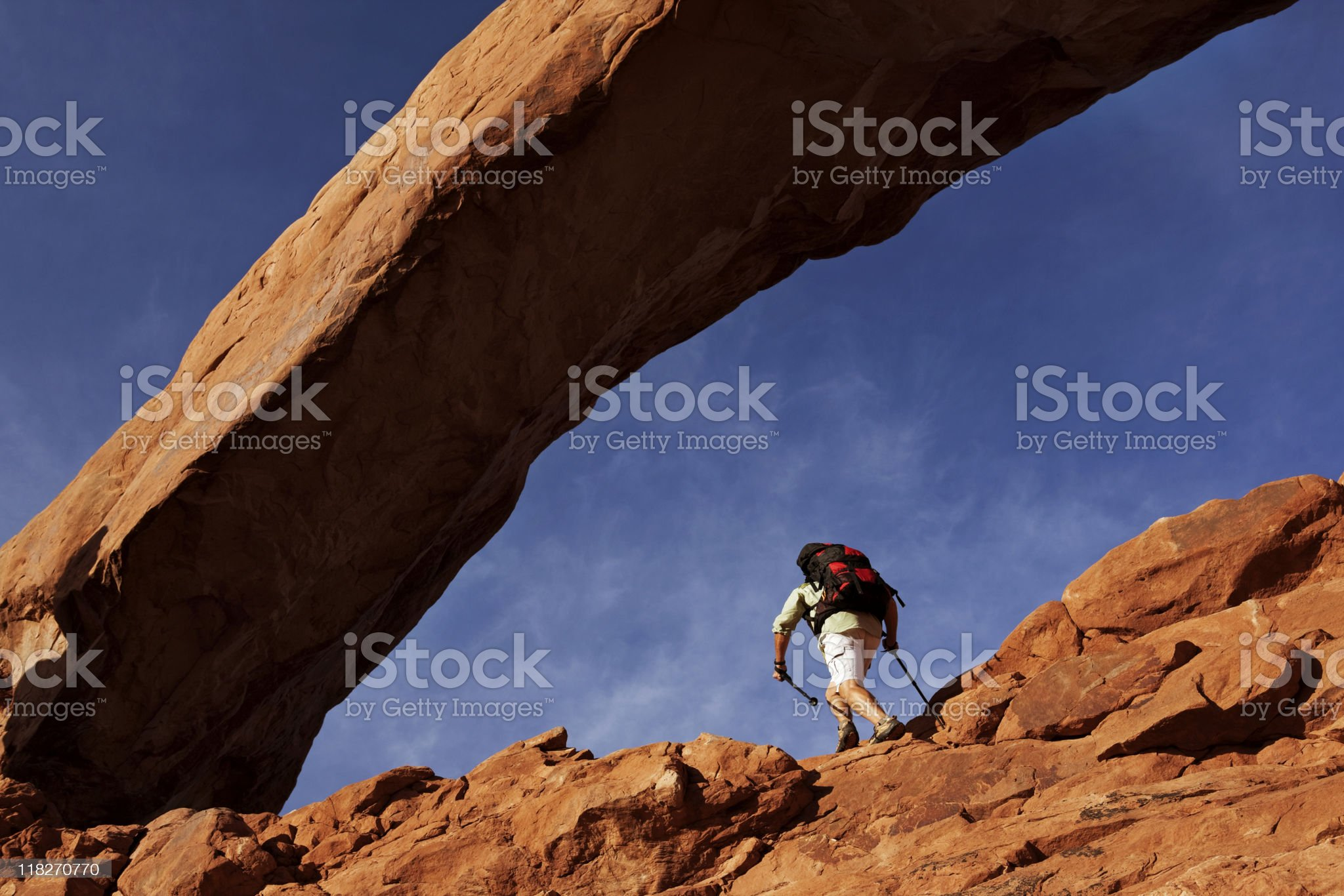 Backpacker Under Huge Arch Hiking On Rocky Ledge royalty-free stock photo