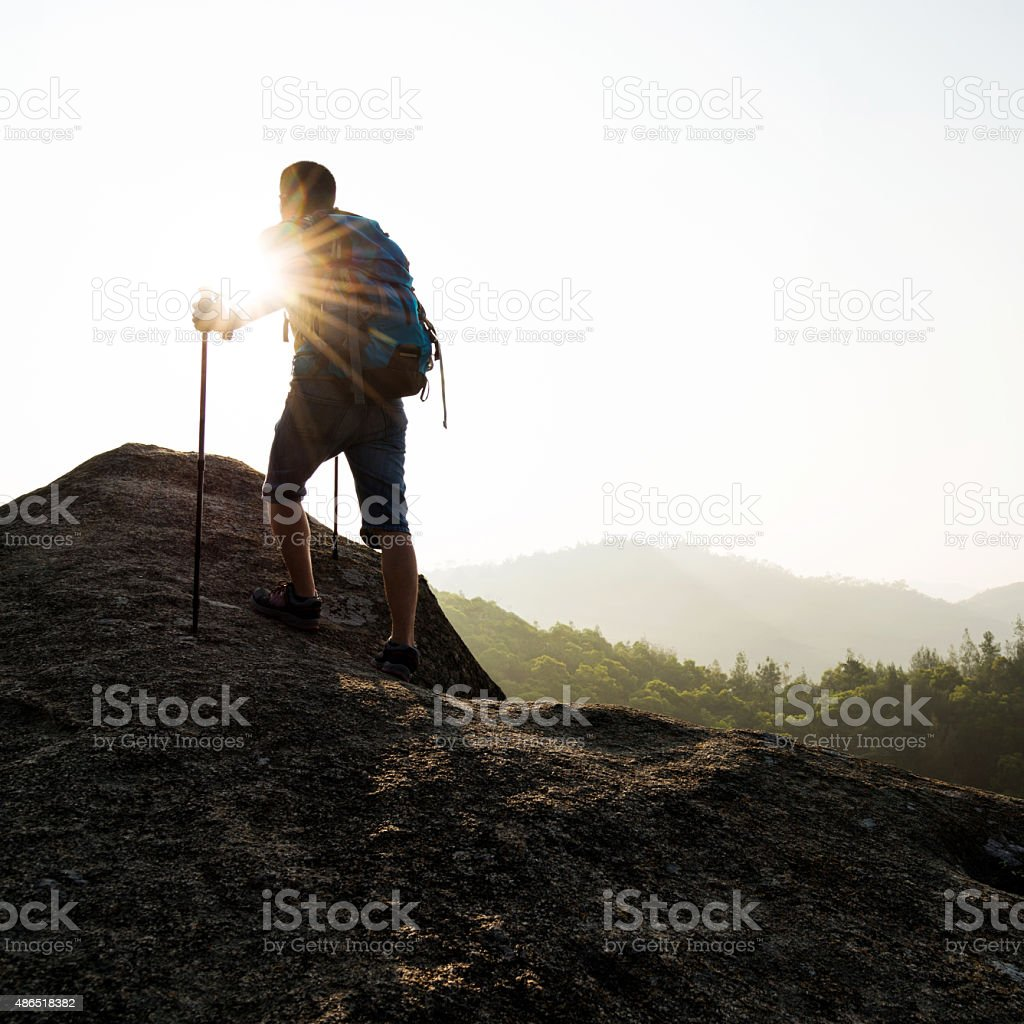Backpacker walking on mountain peak stock photo