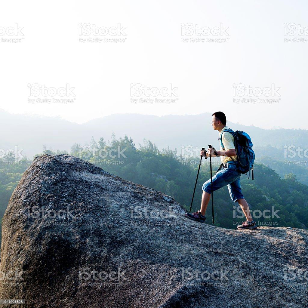Backpacker walking on mountain peak stock photo