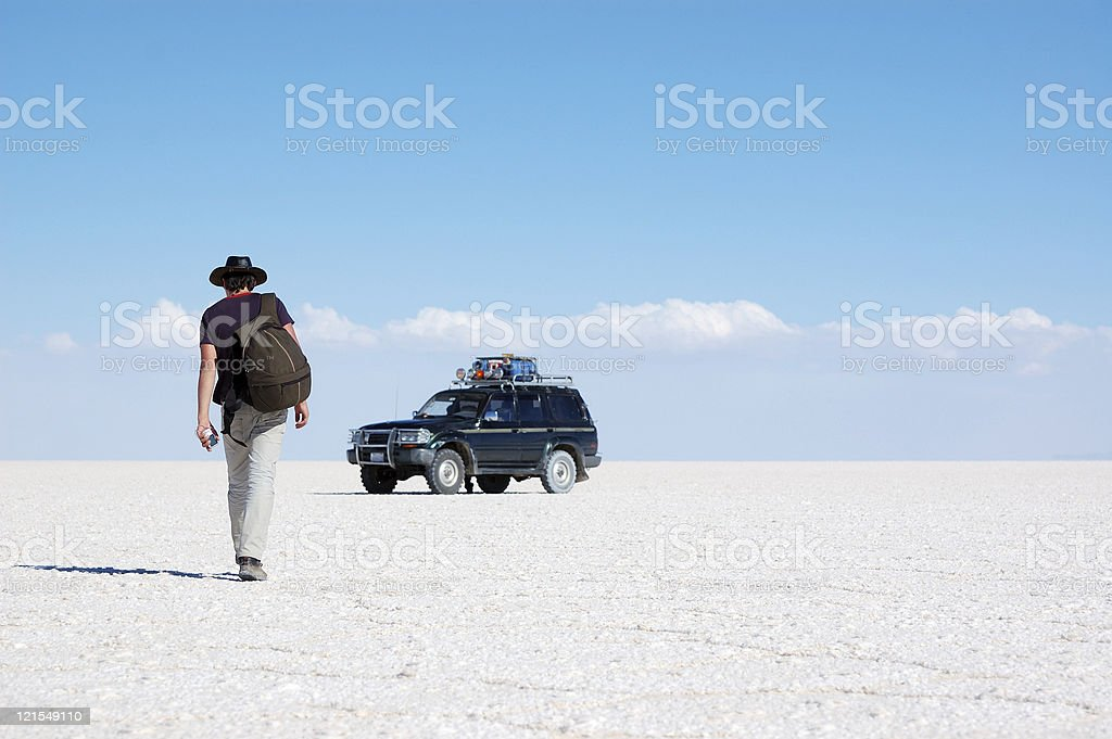 Backpacker walking to the car in salt desert stock photo