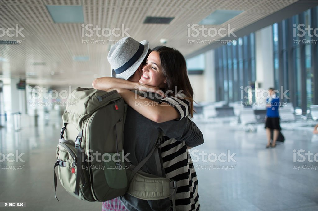 Backpacker welcome hug in the airport. stock photo