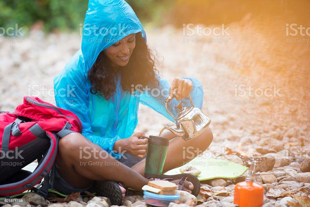 Backpacker woman having lunch break. stock photo