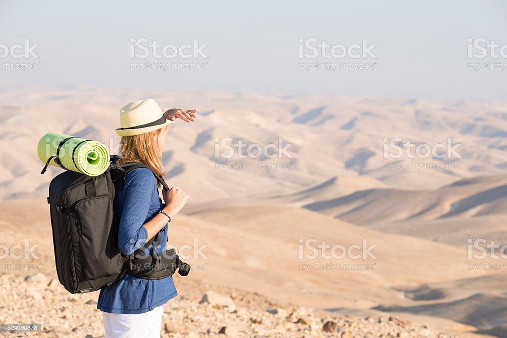 Backpacker woman in desert. stock photo