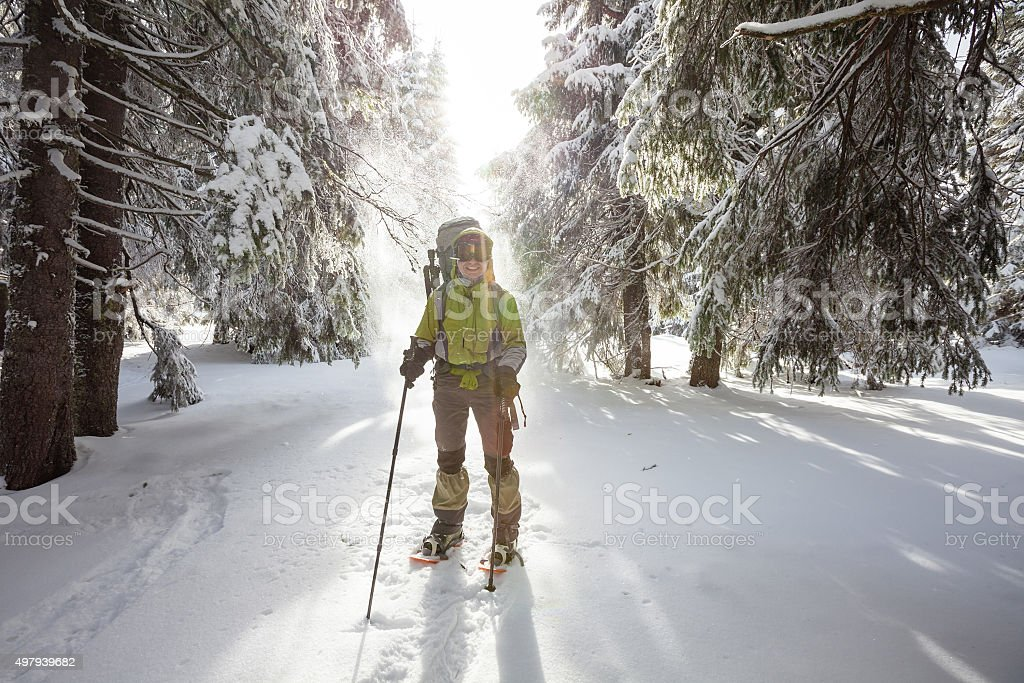 Backpacker woman is walking in forest in wintertime stock photo