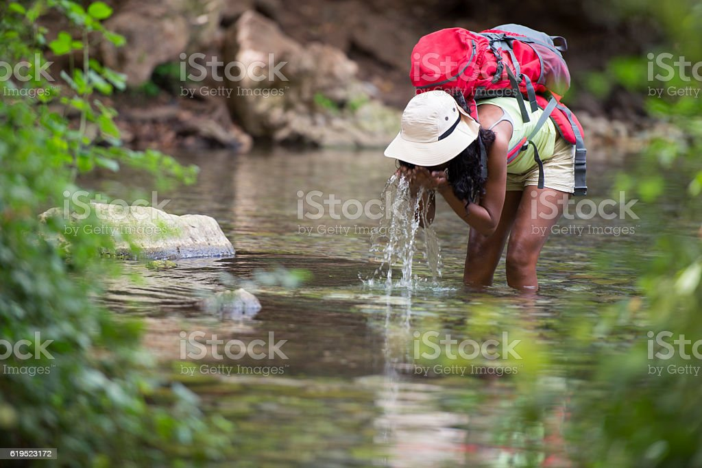 Backpacker woman refreshing her face with spring natural water. stock photo