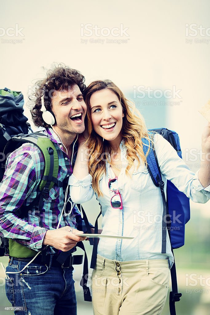Backpackers couple in the city Listening Music Together Outdoors. stock photo