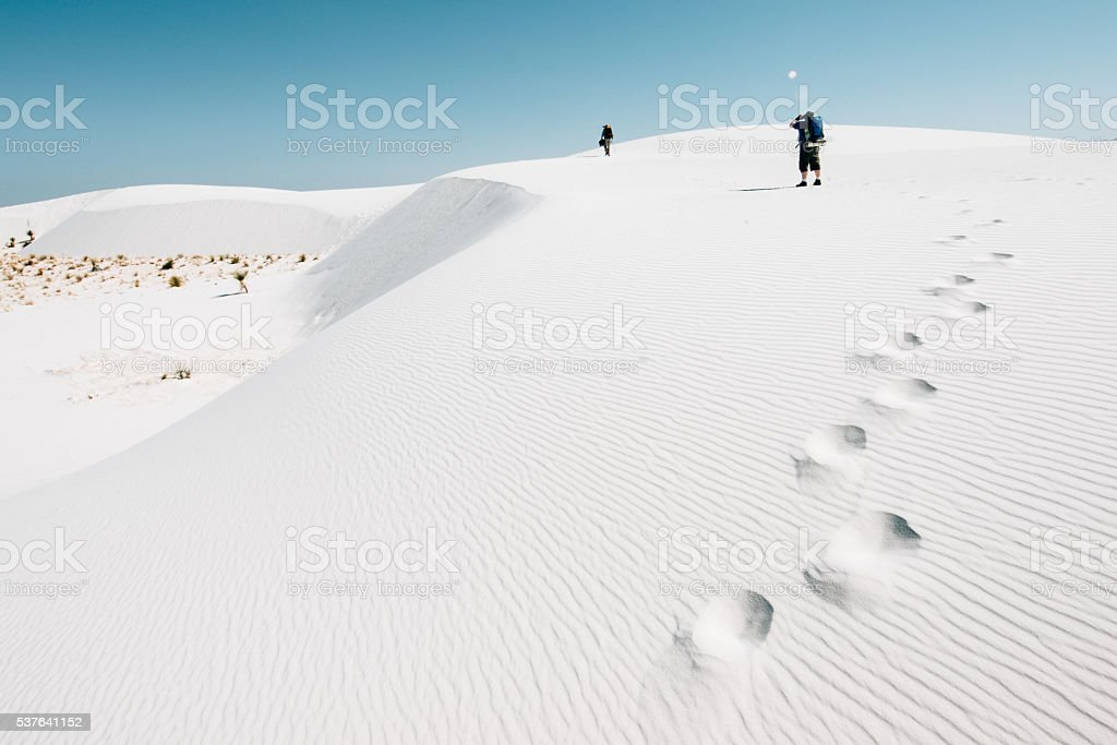 Backpackers hiking on the desert dunes stock photo