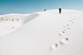 Backpackers hiking on the desert dunes
