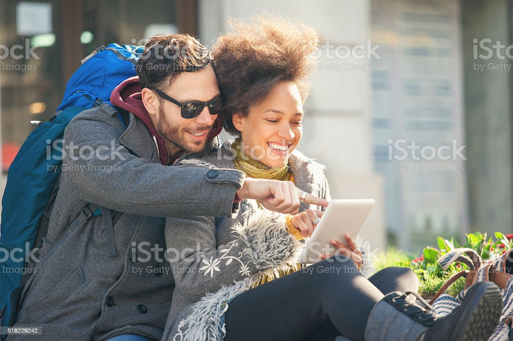 Backpackers in the city using tablet pc stock photo