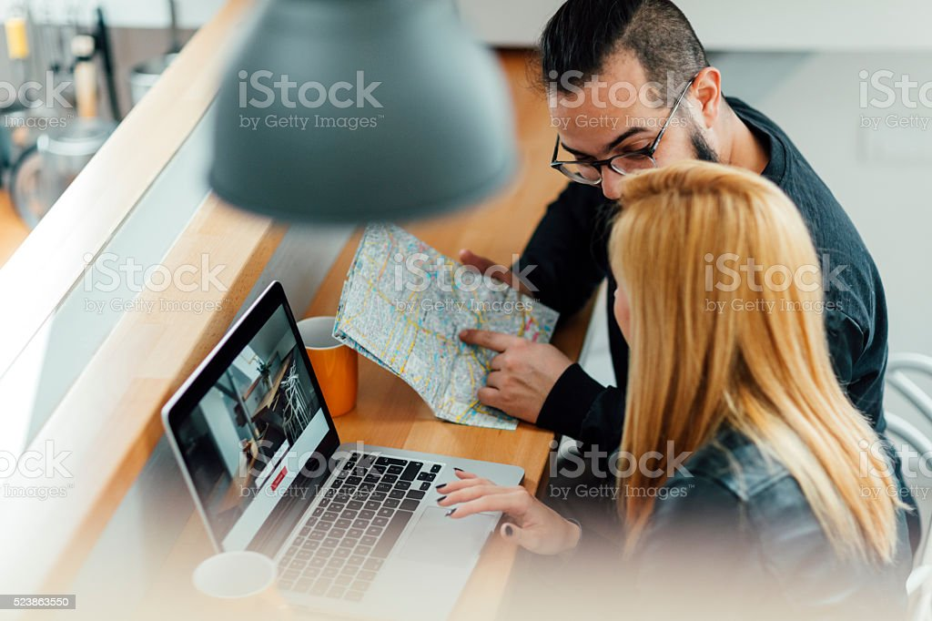 Backpackers Looking For Apartment On Their Laptop. stock photo
