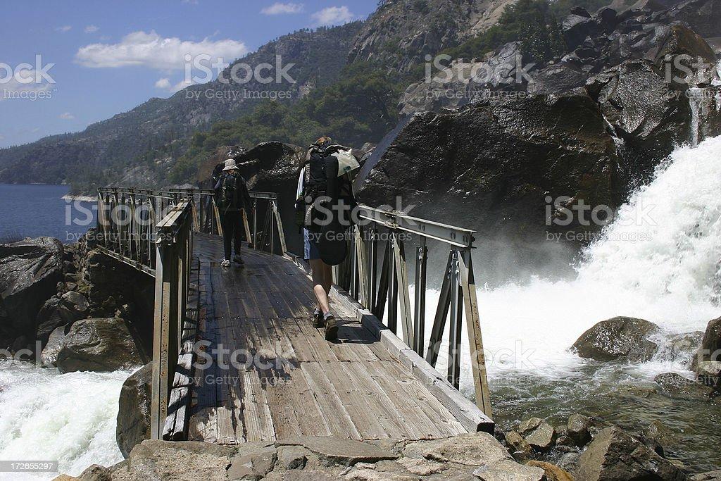 Backpackers on  a bridge stock photo
