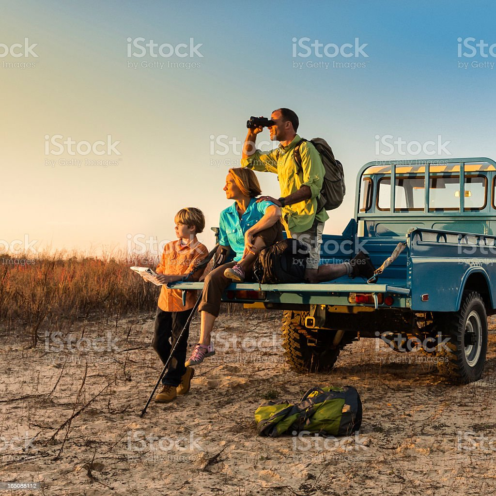 Backpacking family on vehicle at sunset stock photo