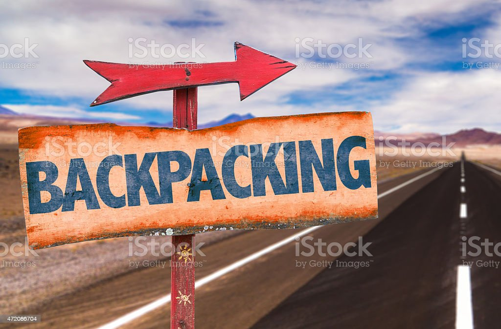Backpacking sign with road background stock photo