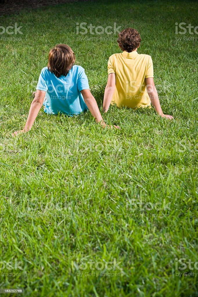 Backs of children sitting on grass royalty-free stock photo