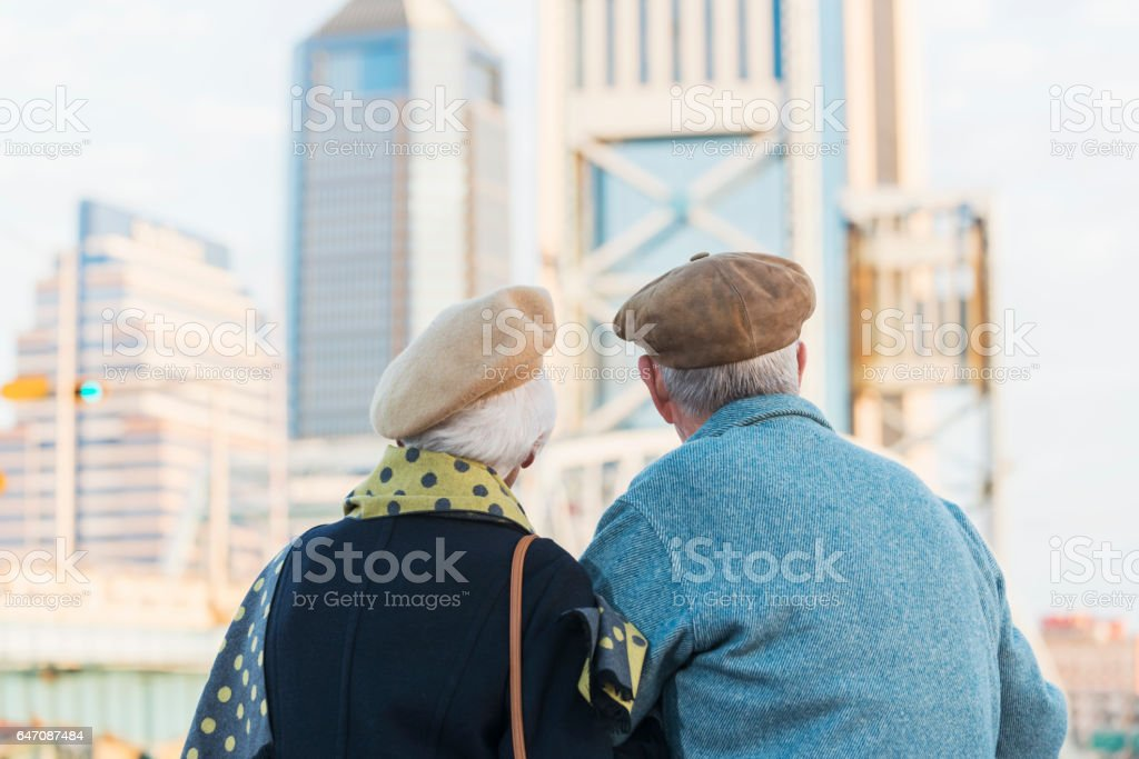 Backs of old couple looking at city view stock photo