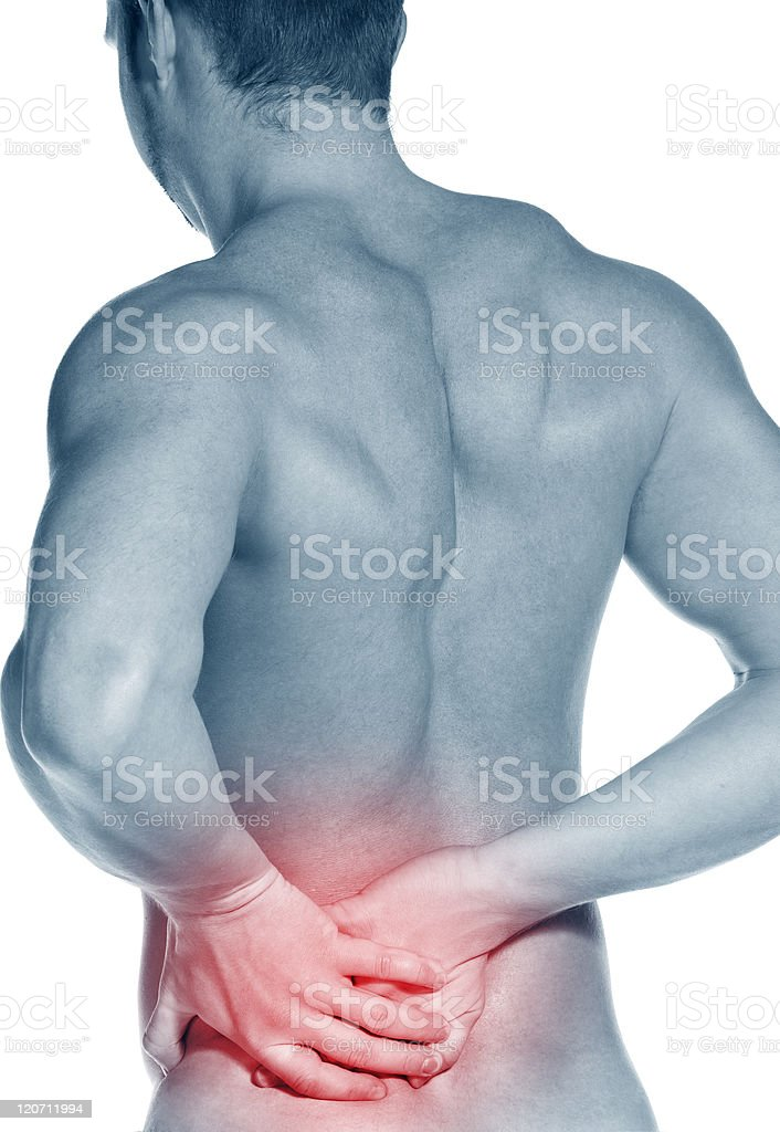 Backside of a naked young man holding his waist in pain royalty-free stock photo