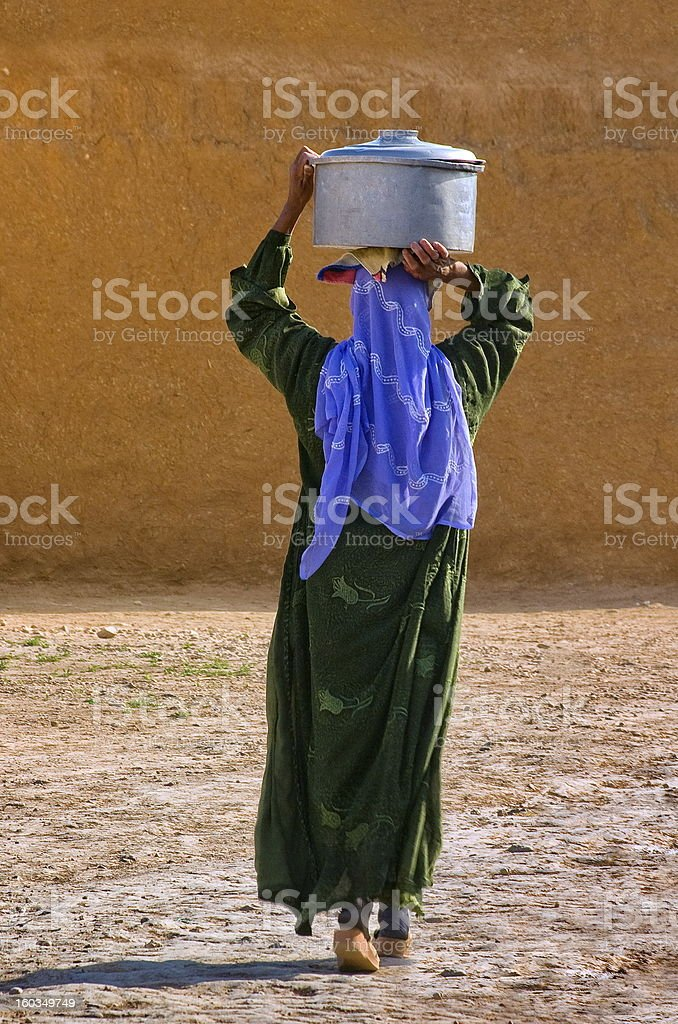 Backside of a woman carrying a pot on her head stock photo