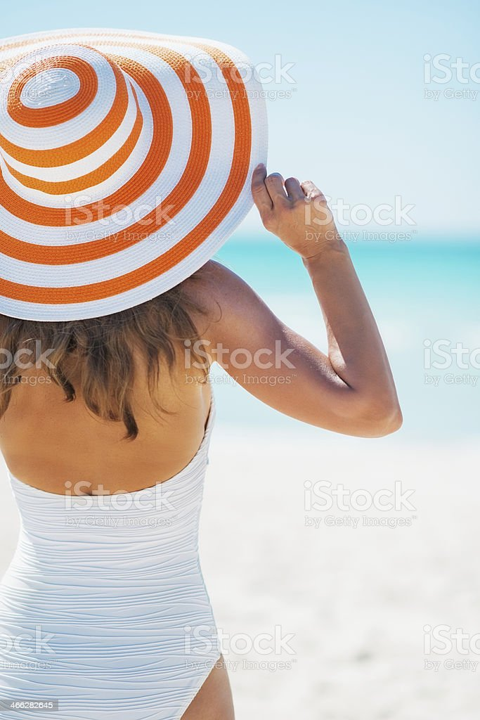 Backside of a woman wearing a large hat at beach stock photo